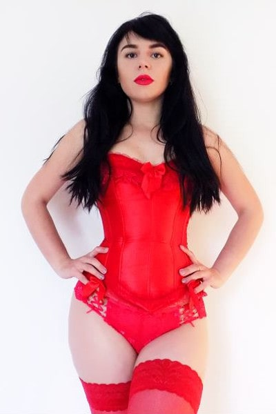 dominant mistress posing in red corset & leggings