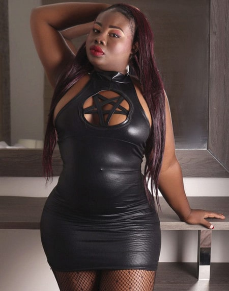 chubby ebony domme posing tight black leather dress