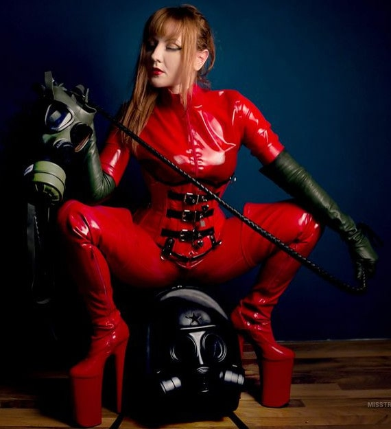 sissy trainer in latex body suit, gloves and high-heel latex boots