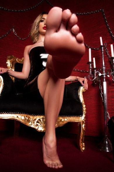 mistress offering her foot to kiss