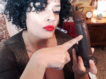 thick mature domme smoking cigarette holding huge dildo